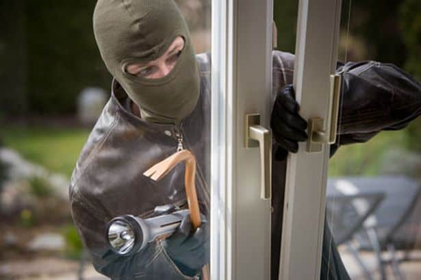Robber breaking into door with crowbar to commit theft.
